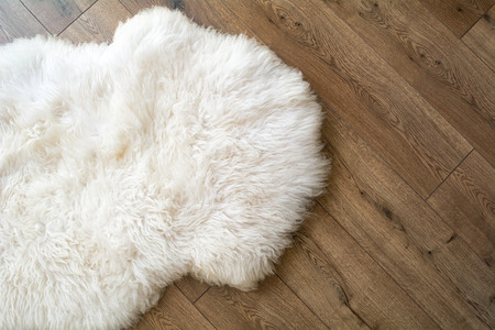 Photo pour Sheep skin on the laminate floor in the room. View from above. - image libre de droit