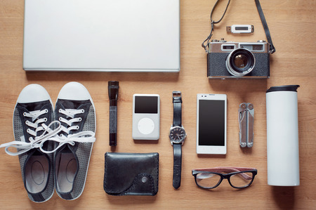 Outfit of modern traveler, student, woman or guy. Overhead of essentials on wooden background: camera, smart phone, glasses, flashlight, laptop, wallet, watch, gumshoes, thermos, multitool, mp3 player