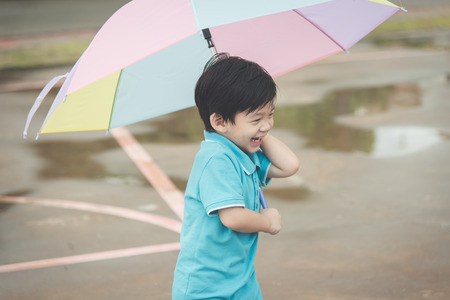 Happy asian boy holding colorful umbrella playing in the park,vintage filterの写真素材