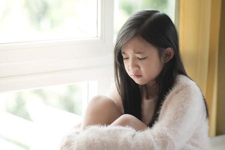 Foto de Portrait of asian beautiful sad girl at the window,vintage filter - Imagen libre de derechos