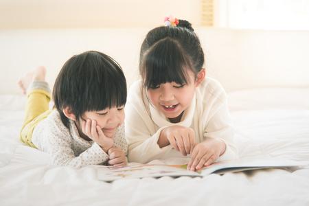 Photo pour Cute asian children reading book on white bed,vintage filter - image libre de droit