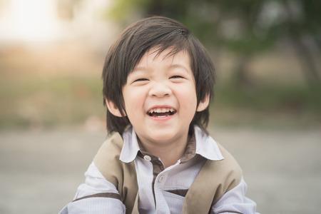 Photo pour Close up portrait of asian boy laughing,vintage filter - image libre de droit