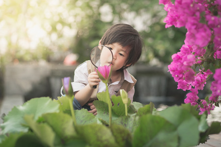 Photo for Asian boy with magnifying glass outdoors,vintage filter - Royalty Free Image