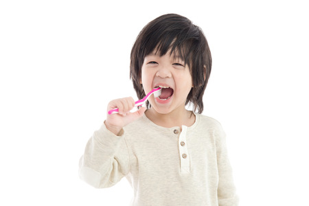 Photo pour Cute asian child brushing teeth on white background isolated - image libre de droit