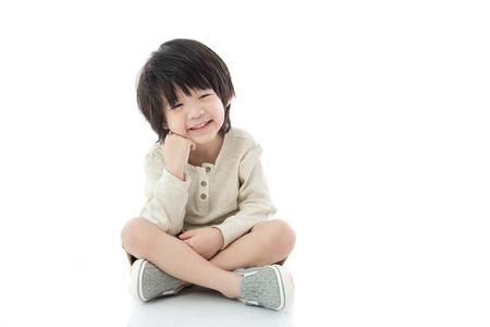 Photo for Happy asian boy sitting on white background isolated - Royalty Free Image