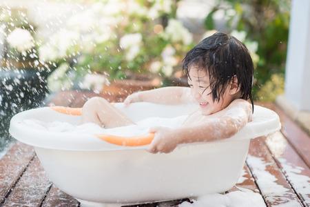 Photo pour Cute asian  child bathing in the garden - image libre de droit