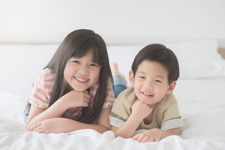Foto de Cute asian children lying on white bed - Imagen libre de derechos