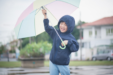 Happy asian boy holding colorful umbrella playing in the park after the rainの写真素材