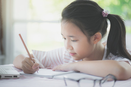 Photo pour Beautiful asian girl writing to diary on the table - image libre de droit