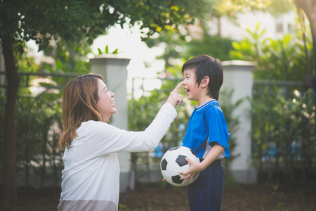 Foto de Asian mother and son Playing Soccer In Park Together - Imagen libre de derechos