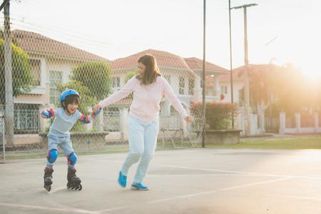 Foto de Asian mother helping her son to playing roller skate in the park - Imagen libre de derechos