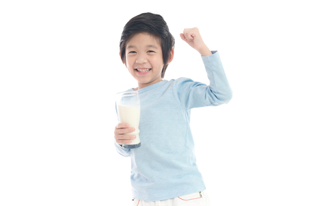 Foto de Asian child drinking milk from a glass on white background isolated - Imagen libre de derechos