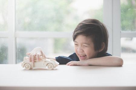 Foto de Cute Asian child playing wooden model car on a table - Imagen libre de derechos