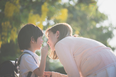 Foto de Asian child whispers something to his mother,back to school - Imagen libre de derechos