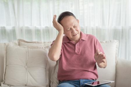 Photo pour Asian old man at home having a headache - image libre de droit