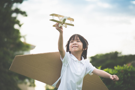 Foto de Cute Asian child playing wooden airplane in the park outdoors - Imagen libre de derechos