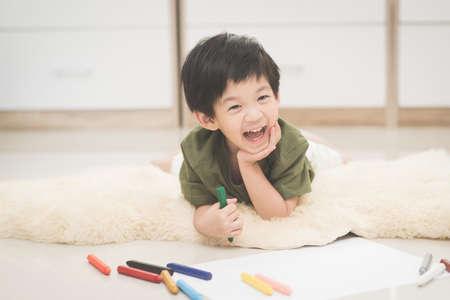 Photo pour Cute Asian child drawing picture with crayon - image libre de droit