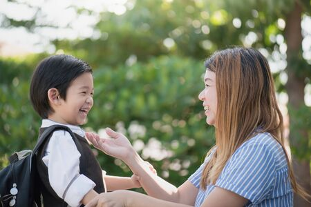 Photo for Asian mother  saying goodbye to her son as he leave for School, back to school concept - Royalty Free Image