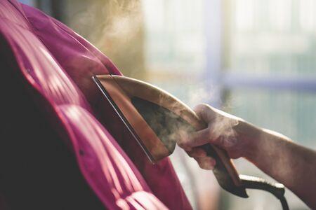 Photo pour Asian woman Woman ironing down jacket with garment steamer - image libre de droit