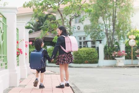 Photo pour Cute Asian children  holding hand  together while  going to the school - image libre de droit