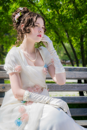 Foto de Portrait of a young bride woman in a historical white dress with a book in hands outdoors in a park on a bench. - Imagen libre de derechos