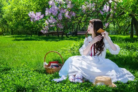 Foto de Nice girl in a white dress sits on a lawn in a park under a bush of blooming lilacs and combes her long hair. - Imagen libre de derechos