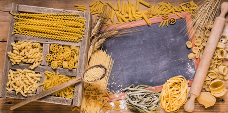 vast assortment of Italian pasta with different sizes and qualities in rustic wooden compartments.space for text