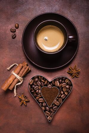 Foto per composition with a cup of espresso, and heart-shaped silhouette with coffee beans and ground coffee - Immagine Royalty Free