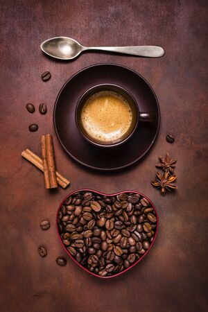 Foto per composition with a cup of espresso, and a heart-shaped bowl with coffee beans - Immagine Royalty Free