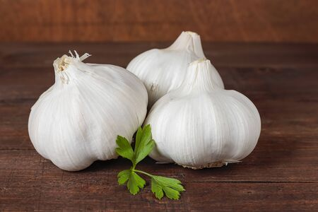 Foto für horizontal view of three garlic heads and parsley leaves on a table and wood background - Lizenzfreies Bild