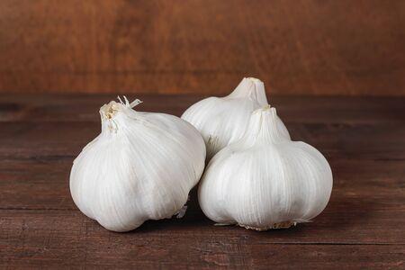 Foto für horizontal view of three garlic heads on a table and wood background - Lizenzfreies Bild