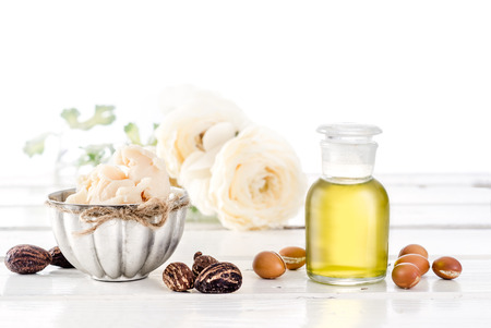 Foto de Still life of Argan oil and fruit and shea butter with nuts on a wooden table with flowers - Imagen libre de derechos