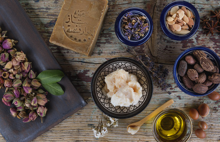 Photo pour Mix of herbs, flower, argan nut and oil, shea nuts and butter, anise and Aleppo soap on wooden table - image libre de droit