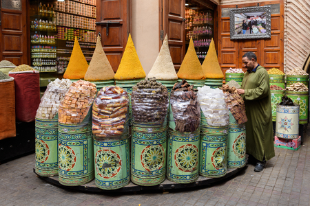 MARRAKECH, MOROCCO - MAY 9,2017: Unidentified man sells spices in his shop in the souq (market) of Marrakech