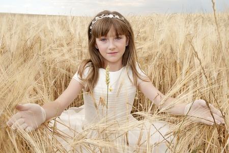 chica con vestido de primera comunión entre la cebada