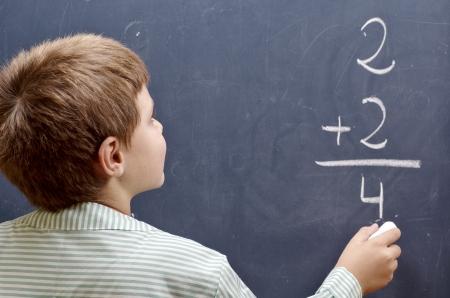 child writing sum on blackboard