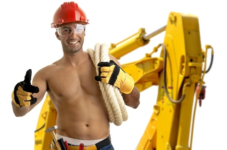 Strong build construction worker with big machine in the background