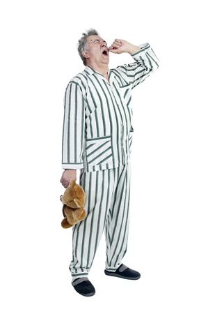Senior man in pajamas with teddy bear isolated in white