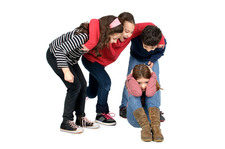 Group of children bullying an isolated child