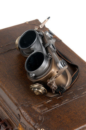 Photo pour Steampunk goggles over a suitcase isolated in white - image libre de droit