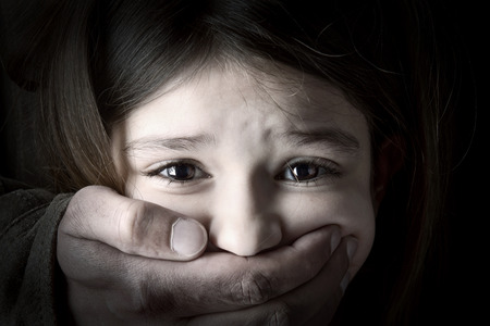 Scared young girl with an adult man s hand