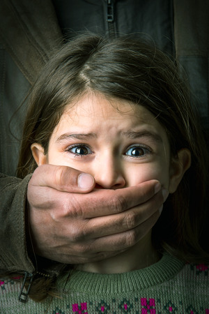Photo pour Scared young girl with an adult man's hand covering her mouth - image libre de droit