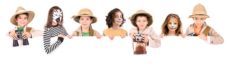 Children's group in safari clothes and face-paint over a white board