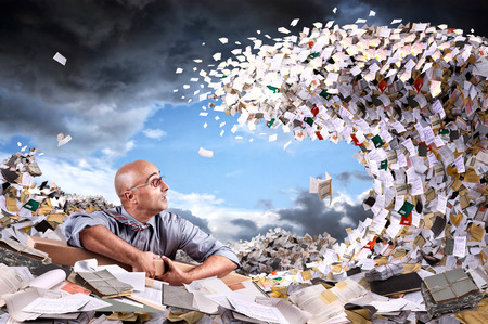 Photo for Castaway businessman in a sea of papers and files - Royalty Free Image