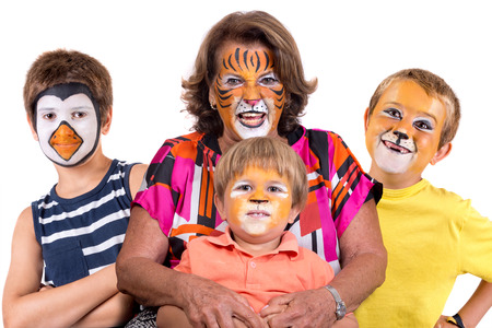 Photo for Children's group and grandmother all with animal face-paint isolated in white - Royalty Free Image