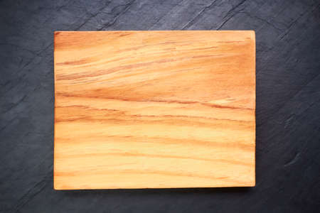 Photo for Brown wooden cutting board on black slate. Wood texture - Royalty Free Image