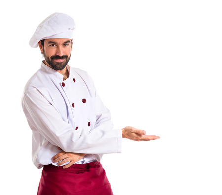 Photo for Chef presenting something over white background - Royalty Free Image