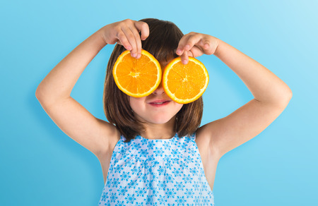 Photo pour Girl holding orange slices as glasses - image libre de droit