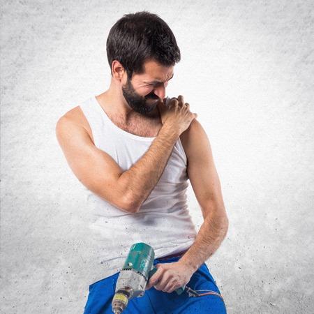 Photo pour Young electrical technician with a drill with shoulder pain - image libre de droit