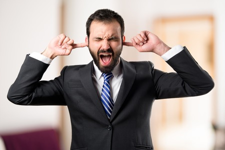 Photo pour business man covering her ears over white background - image libre de droit